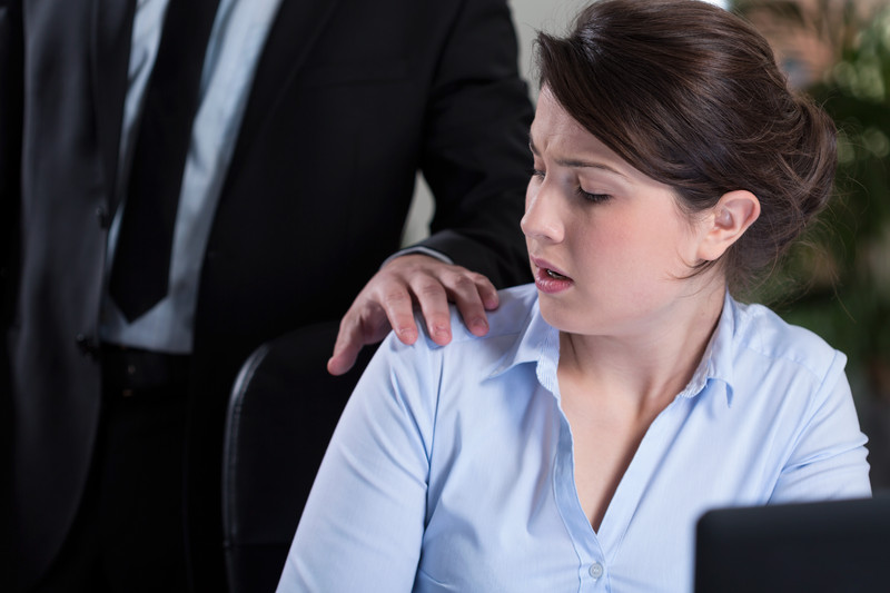 Male office worker touching shoulder of female office worker