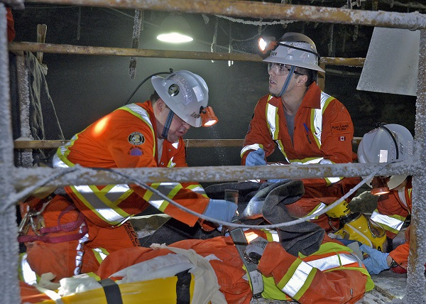 Two mine rescue volunteers perform first aid