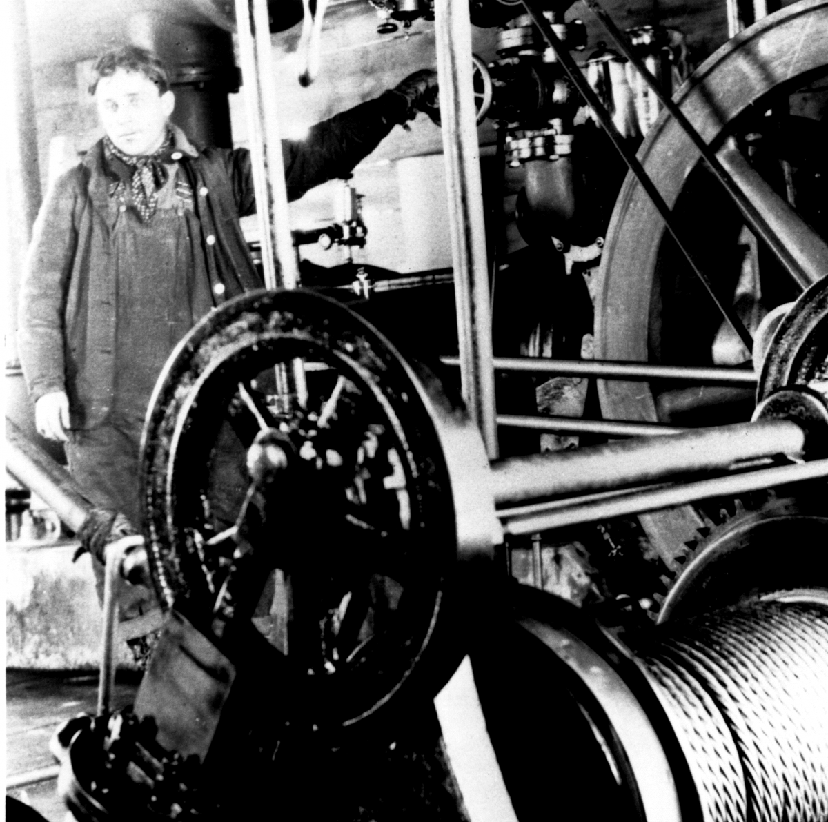 Black and white photo of worker standing at paper mill machinery circa 1900