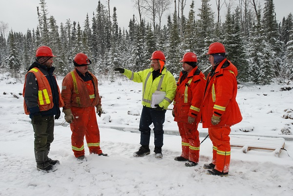 Group of workers standing outdoors in winter forest setting