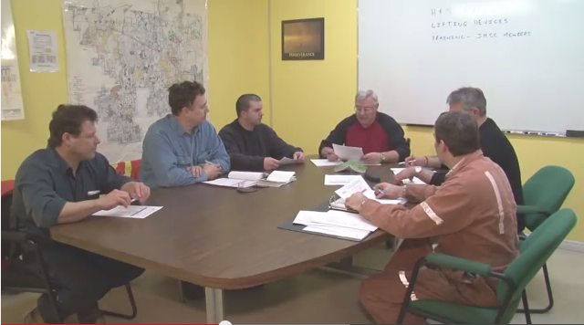 Group of workers gathered around table for meeting