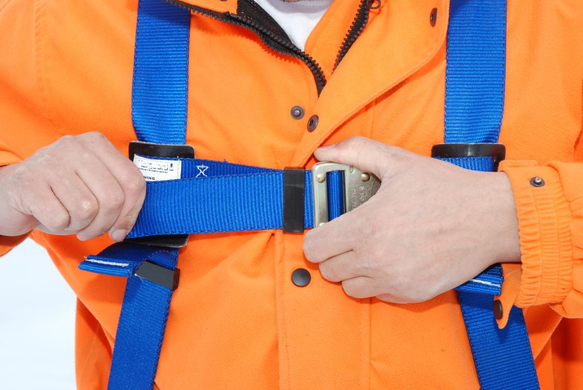 Worker tightening fall arrest harness chest strap