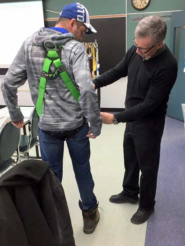 Student tries on fall protection harness with help of instruction