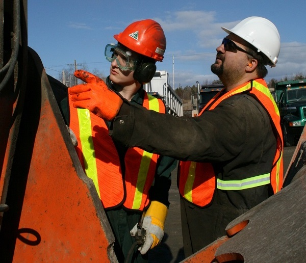 Supervisor training younger worker in outdoor industrial setting