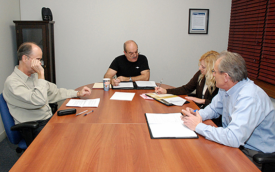 Group of people sitting around boardroom table