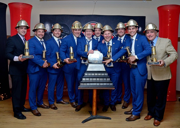 Group of men wearing gold hardhats with large trophy in front