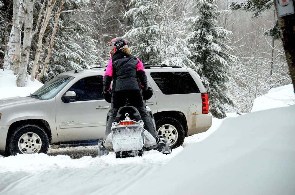 snowmobiler waiting to cross road